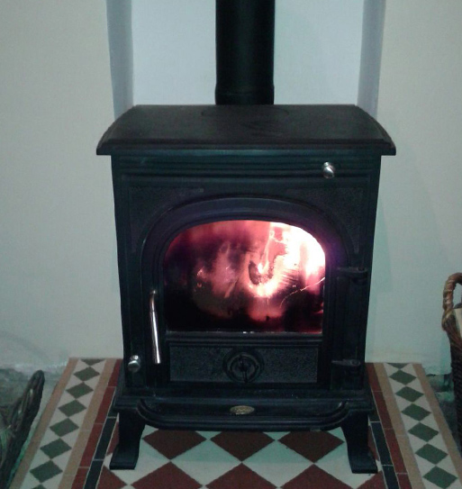 Wood burning stove with flames from the fire visible through the glass